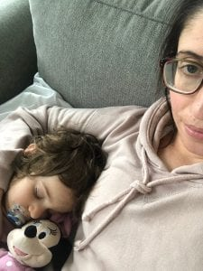 Woman taking a selfie with her young child sleeping by her side