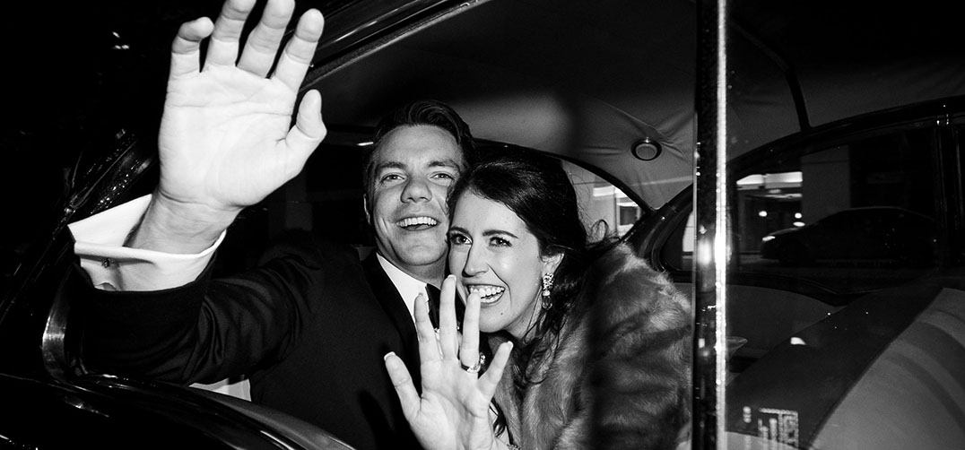 Bride and groom waving laughing and waving goodbye to guests as they are in their getaway car, ready to drive off