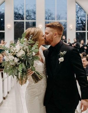 Bride and groom kissing as they walk out the chapel affer their ceremony, and bride is holding her bouquet, as guests look on