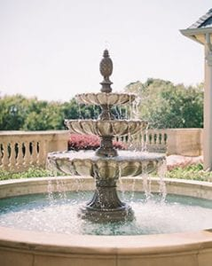 A flowing three tier outdoor fountain on The Olana property, cascading water into its base