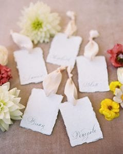 Names on handtown paper with calligraphy script, with blush ribbon on a blush base and flowers