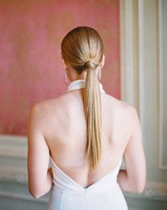 The back of a woman with a long ponytail in a backless white jumpsuit, in a room with pink and gold wallpaper and white crown molding