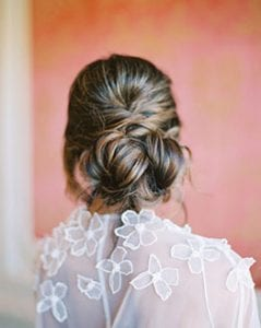 Closeup of a woman's highlighted updo, wearing a cape with floral detail, with a pink backdrop