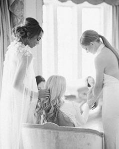 Women in white helping each other get ready. One is brushing another's hair, one is helping put on a bracelet at The Olana