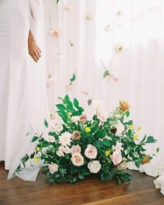 Cluster of greenery and flowers on a wooden floor, next to a woman in white dress and white drapery with hanging flowers