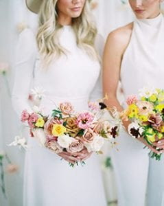 Women in white dresses holding bouquets of flowers in yellow, pink and white