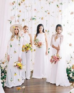 Four women in white dresses, in a room with all white drapery, with flowers hanging, and clusters of greenery and flowers on a wooden floor