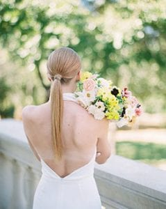 The back of a woman with a long ponytail in a backless white jumpsuit, holding a bouquet with a stone railing in the background