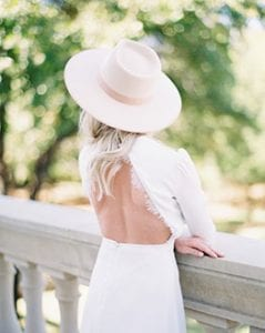 Women in a backless white dress, wearing a hat, with her back to the camera, with her arms resting on a stone railing