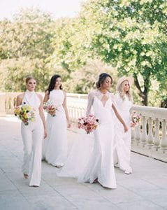 Four women in white, holding bouquets and walking on a paved patio with a stone railing and trees in the background