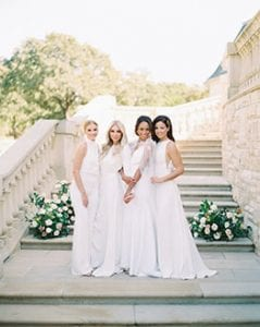 Four women standing in white, holding onto each other and looking at the camera, with a grand stone staircase in the background and clusters of greenery and flowers behind them