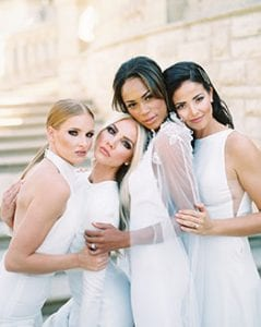 Four women standing in white, holding onto each other and looking at the camera