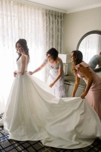 Mother of the bride helping her daughter zip up her wedding dress as bridesmaids in blush look on