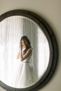 Bride putting on her earrings as she's wearing a scooped low back gown with giant white satin bow at The Adolphus hotel