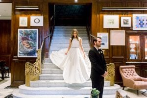 Bride walking down a flight of stairs at the Adolphus hotel in he white wedding gown with a white bow, as her groom waits at the bottom in a black tux for their first look