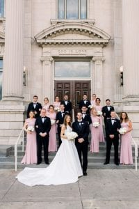 Bride, groom and their bridal party wearing black and blush standing in front of the church