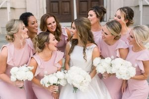 Bride in a cascading white gown with her bridesmaids in blush, holding their all white bouquets in front of the church