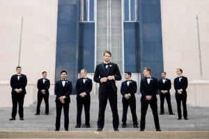 Groom in a black tux, standing with his groomsmen, wearing black suits, standing in front of the church