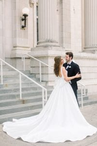Bride in a cascading white gown and groom in his black tux standing in front of the church, looking at each other
