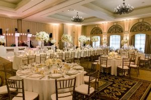Wedding reception in the ballroom of The Adolphus hotel with white dance floor, white band stage and head table, guest tables