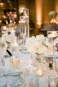 Floating candles on tall clear votives with white floral centerpieces on a table