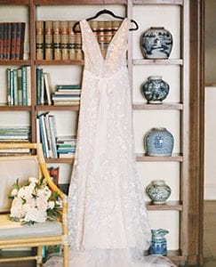 Wedding dress hanging on a bookshelf with the bridal bouquet resting on a chair beside it