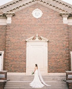 Bride standing in front of a brown chapel
