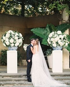 Groom gives bride a kiss on her cheek at their wedding ceremony altar