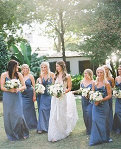 Bride and her bridesmaids on their way to the ceremony laughing and carrying their bouquets