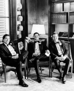 Groom and groomsmen smiling while relaxing in chairs before the wedding
