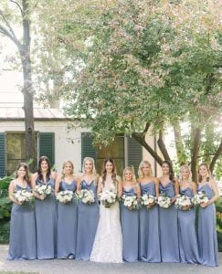 bride and her nine bridesmaids smiling with their bouquets