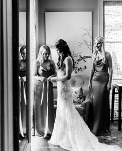 Bridesmaids helping the bride put on her dress on her wedding day