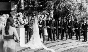 Wedding ceremony taking place at a botanical garden with bride groom their bridal party