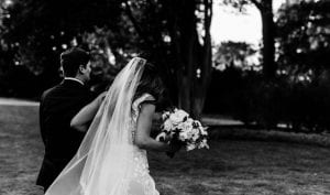 Bride and groom walking away from their garden ceremony