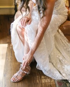 Bride putting on a strappy sandal on her wedding day
