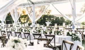Tables and chairs set up under a tent for a wedding reception