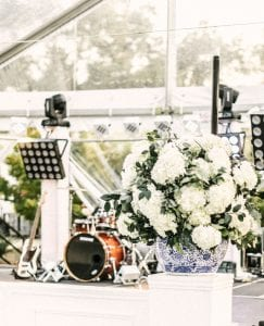 Band setup on a stage at a wedding with a flower arrangement in front