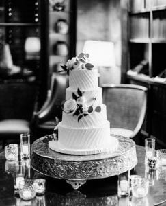 A four tier wedding cake decorated with flowers and greenery on a cake stand surrounded by clusters of candles
