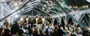 Band is playing while guests at a wedding dine under a tent during the reception