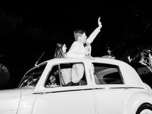 Bride and groom waving goodbye from the roof of a Rolls Royce
