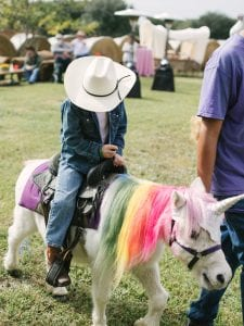 a pony with its mane dyed in all the colors of the rainbow, wearing a unicorn horn while a boy rides it