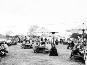 Guests enjoying a meal on picnic tables in a field, with umbrellas and heaters
