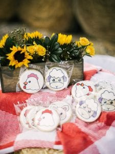 Cookies that have farm animals printed on them, with a sunflower arrangement in the background