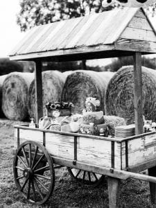 Cake and dessert set up on a wooden floral cart, with haybales in the background