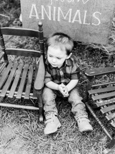 """A boy sitting in between two rocking chairs, in front of an """"Animals"""" sign"""