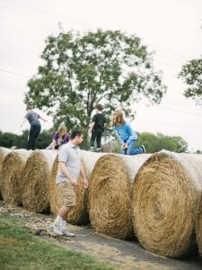Kids playing on haybales while an adult watches on