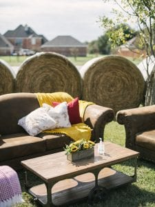 Brown leather ounge furniture, with cushions and a mustard throw with haybales in the background