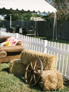Wooden wheel resting on haybales, with lounge furniture in the background