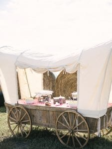 BBQ buffet spread on a wagon with haybales in the background