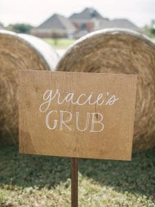 "Wooden sign with ""Gracie's Grub"" on it, and haybales in the background"